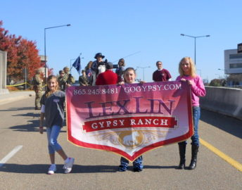Lexi, far right, and her younger sister Lindie pictured during a Veteran's Day parade.